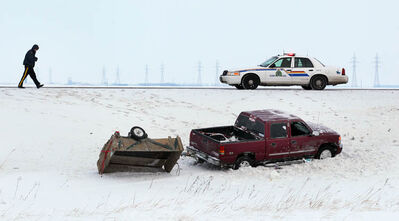 An RCMP member documents the scene of a rollover on the Trans Canada West of Winnipeg Friday morning.  At least one was taken to hospital. Icy roads were an issue as warmer temps eased frost out of frozen roads