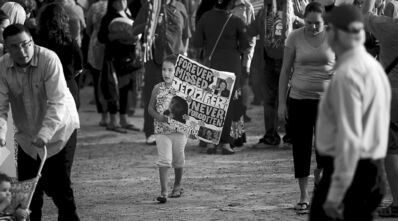 A youngster carries a banner in memory of a missing woman during a vigil Tuesday in memory of Tina Fontaine and Faron Hall.