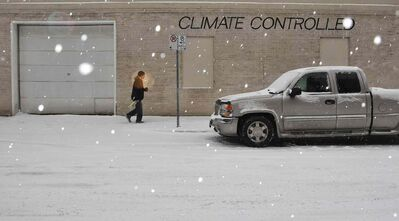 A pedestrian takes a chilly stroll in downtown Winnipeg during the steady snow Sunday morning