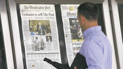 A passerby views the front page of the Washington Post on Tuesday, a day after it was announced Amazon.com founder  Jeff Bezos bought the paper for $250 million.