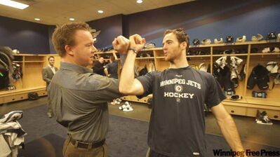 Mark Flood (right) teaches reporter Geoff Kirbyson one of the Jets' not-so-secret secret handshakes.