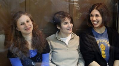 In this Oct. 1, 2012 photo, feminist punk group Pussy Riot members, from left, Maria Alekhina, Yekaterina Samutsevich and Nadezhda Tolokonnikova sit in a glass cage at a court room in Moscow, Russia. THE CANADIAN PRESS/AP, Sergey Ponomarev