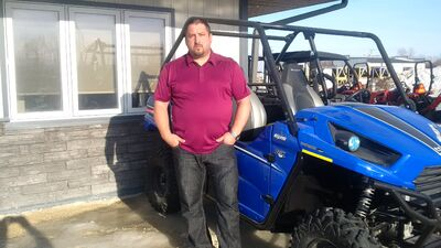 Derek Roth stands with an ATV similar to the one that was stolen Tuesday.