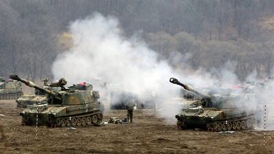 South Korean marine's K-55 self-propelled howitzers are covered by smoke during a military exercise in the border city between two Koreas, Paju, north of Seoul, South Korea, Tuesday, April 2, 2013. North Korea vowed Tuesday to restart a nuclear reactor that can make one bomb's worth of plutonium a year, escalating tensions already raised by near daily warlike threats against the United States and South Korea. (AP Photo/Lee Jin-man)