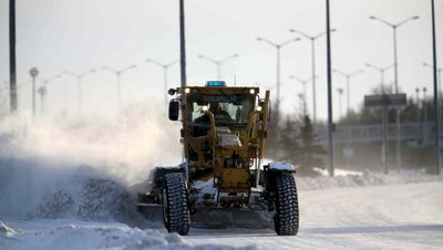 A snow grader clears a lane on the William R. Clement parkway in Winnipeg on Saturday.