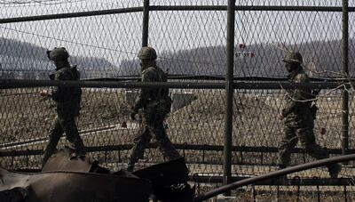 South Korean army soldiers patrol along a barbed-wire fence at the Imjingak Pavilion near the border village of Panmunjom, which has separated the two Koreas since the Korean War, in Paju, north of Seoul, South Korea, Friday, March 15, 2013. The Koreas' border can seem a surreal place at the best of times — part tourist trap, part war zone. An amusement park, fast-food joints and kitschy souvenir shops mix with an ever-present Cold War tension that is higher now than it has been in years, following North Korean outrage over U.N. sanctions and joint U.S.-South Korean military drills.(AP Photo/Lee Jin-man)