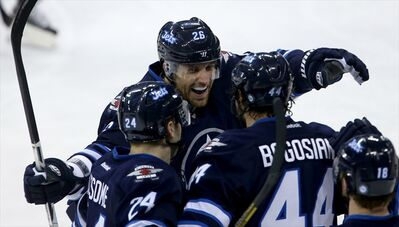 Winnipeg Jets' Blake Wheeler (top) celebrates with Grant Clitsome (left) and Zach Bogosian after he assisted on Bogosian's goal during the first period.Wheeler re-signed with the Jets Friday; Bogosian did the same Monday.