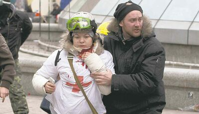Olesya Zhukovska is helped after being shot in the neck by a sniper's bullet in Kyiv's Independence Square Thursday.