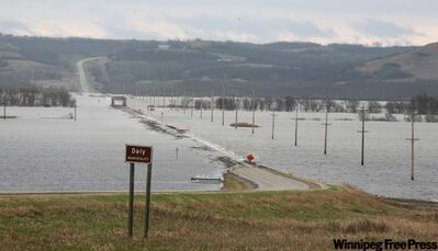 The swollen Assiniboine River covers the valley floor, consuming the bridge on Highway 250, west of Brandon, on Tuesday.