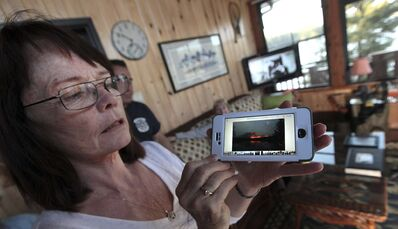 PHIL HOSSACK / WINNIPEG FREE PRESS</p><p>Sandy Fisette displays photos taken across Caddy Lake's Green Bay of the fire that forced their evacuation. Her husband, Grant, is a volunteer firefighter who fought to ensure the safety of the cottages.</p>