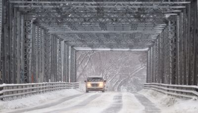 A vehicle drives over the Redwood Bridge as the snow continues to fall Wednesday. A snowfall warning is in effect for the Winnipeg area. Up to 10 cm of snow will fall and the wind will gust up to 60 km/h.
