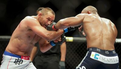 Dan Henderson (left) takes a shot from Rashad Evans during their light heavyweight main card fight at UFC 161.