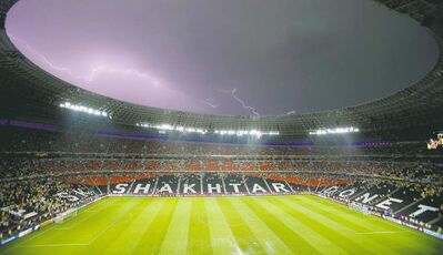 Lightning flashes over the stadium after the weather suspended the Euro 2012 soccer championship Group D match between Ukraine and France in Donetsk, Ukraine, Friday, June 15, 2012.