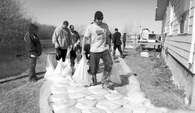 Volunteers help erect a sandbag dike around a home on Peguis First Nation in 2011. Flooding is expected again this year.