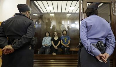 FILE - In this Aug. 17, 2012 file photo, feminist punk group Pussy Riot members, from left, Yekaterina Samutsevich, Maria Alekhina and Nadezhda Tolokonnikova sit in a glass cage at a court room in Moscow, Russia. Jailed Pussy Riot member Nadezhda Tolokonnikova said in an interview released by Germany's Der Spiegel magazine on Sunday, Sept. 2, 2012 that she regrets nothing about the band's anti-government performance in a cathedral that got them convicted of hooliganism and sentenced to two years behind bars. (AP Photo/Sergey Ponomarev, File)