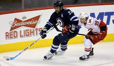 Winnipeg Jets' Dustin Byfuglien leads Carolina Hurricanes' Patrick Dwyer around the net during the first period of Saturday afternoon's game at the MTS Centre.
