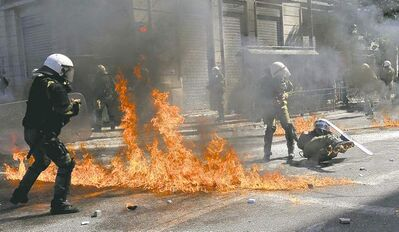 nikolas giakoumidis / the associated press A firebomb explodes among riot police during clashes in the streets of Athens, Greece, Wednesday.