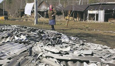 A woman looks at roof debris Friday at the site of a fire at a psychiatric hospital outside Moscow.