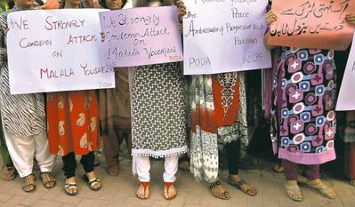 Women in Islamabad, Pakistan, protest the Taliban attack on schoolgirl Malala Yousufzai. The banner at right reads, 'The Taliban is afraid of an unarmed girl.'