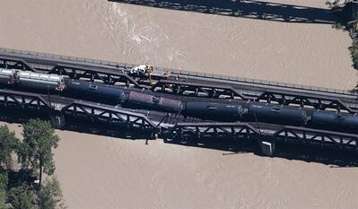 Crews work at the scene of a rail bridge collapse in Calgary on Thursday, June 27, 2013. THE CANADIAN PRESS/Larry MacDougal