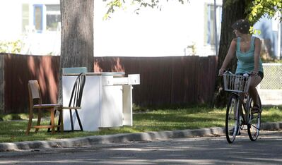 A passerby checks out some chairs and a desk on Sherburn Street during giveaway weekend in 2011.