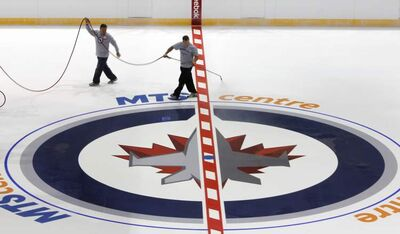 Derek King, manager of ice operations mists with water the new Winnipeg Jets fabric logo placed at center ice in the MTS Centre Friday.   (WAYNE GLOWACKI/WINNIPEG FREE PRESS) Winnipeg Free Press Sept.1  2011