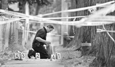 A police officer collects evidence from the scene of suspected gang violence in the inner city.