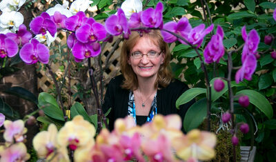 Wendy Chaytor is surrounded by a display of orchids.