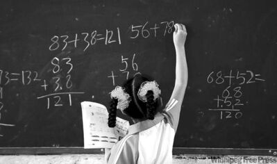 A girl writes on a chalkboard during math class at an experimental school in Beijing.