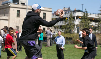 Buck Pierce plays football with schoolkids on the University of Winnipeg campus Wednesday afternoon. BELOW: He discusses strategy with Tom Ali, 10. The U of W has made Pierce and former Bomber Dave Donaldson adjunct coaches for the Inner City Youth Football Program. after it was announced he would be an adjunct coach with the University of Winnipeg and assist Dave Donaldson with his Inner City Youth Football Program.