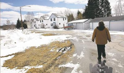 Ingrid Bauer walks through a near-empty town of Point du Bois. The remaining residents must be gone by 2015.