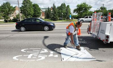 City crew paint bicycle path signs Sunday morning in Charleswood for Winnipeggers looking to go cycling on a perfect summer day.