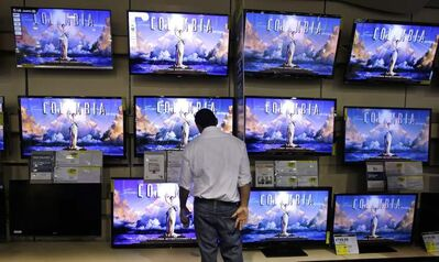 A customer looks at televisions at a Best Buy store last year. The CRTC says 8.7 million households have basic television service.