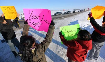 Members of Sandy Bay First Nation use a blockade on the Trans-Canada between Highway 16 and Road 42 West to protest budget bill C45 on Saturday.