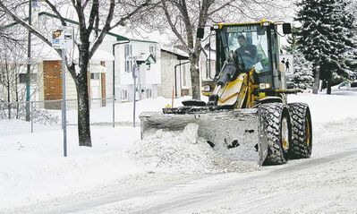 Mike Deal / Winnipeg Free PressA front-end loader clears snow from around a bus stop on Burrows Avenue Monday morning.
