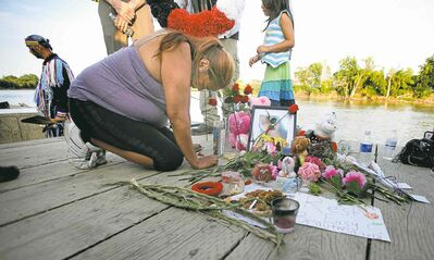 Lana Fontaine, an aunt of Tina Fontaine (below), weeps at a memorial near the Red River where the 15-year-old's body was recovered Sunday.