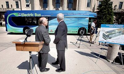 Premier Greg Selinger (right) and Innovation, Energy and Mines Minister Dave  Chomiak check out the new electric bus at the unveiling Friday at the legislature.
