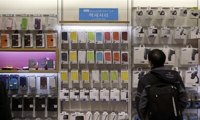 A man looks at the accessaries of Samsung Electronics' Galaxy products at a showroom of its headquarters in Seoul, South Korea, Jan. 8, 2013. THE CANADIAN PRESS/AP, Lee Jin-man