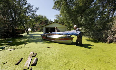 Albert Jacobs (front) pushes his boat with help from his son Dave through stagnant water around the elder Albert's home at Twin Lakes Beach on Lake  Manitoba in 2011. Lake Manitoba communities are again facing the threat of flooding.
