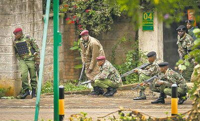 Armed police take cover behind a wall during a bout of gunfire outside the Westgate Mall in Nairobi, Kenya, on Monday, Sept. 23, 2013. (Ben Curtis / The Associated Press)