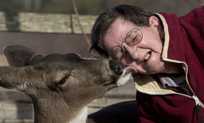 Janet Schwartz gets a kiss from her pet deer Bimbo at their home near Ucluelet, B.C., Saturday, January, 19, 2013. THE CANADIAN PRESS/Jonathan Hayward