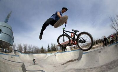 Yarade Garand, 18, performs tricks on his BMX bike at the skate park at The Forks on a warm Saturday afternoon.