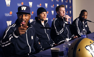 New Winnipeg Blue Bombers' defensive back Korey Banks mugs for the camera at the conclusion of a press conference at Investors Group Field Thursday. Joining him at the podium are, from left, wide receiver Nick Moore, quarterback Drew Willy and wide receiver Cory Watson.