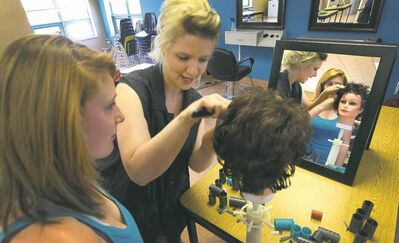 Instructor Jennifer Kreshewski (centre) works with Rossburn Collegiate student Taylor Shmyr in the cosmetology program.