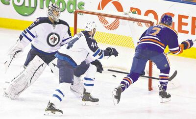 Jets goalie Ondrej Pavelec and D-man Zach Bogosian hustle to reach the general vicinity of the net too late in Edmonton on Monday.