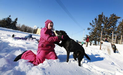 Student Celina Summerfeld hugs Dakota, the school dog, during recess last winter.