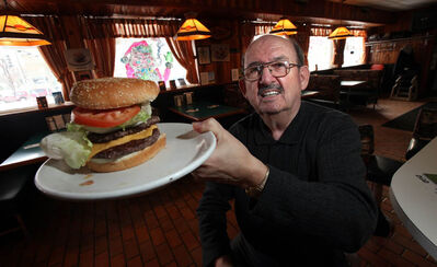 John Ginakes shows off one of his signature burgers at the Thunderbird Restaurant.