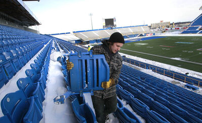 Garrett Iverson helps remove seats purchased by season ticket holders in Canad Inns Stadium.