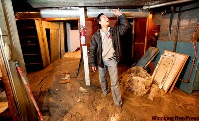Andy Chan, owner of Genesis Hair Design at 498 Bowman Ave., stands in muck in the basement of his business caused by a nearby water-main break.  after  at Watt shows how high the water came (7ft) after a water main break happened right next to his building.    See Lindor�s story.