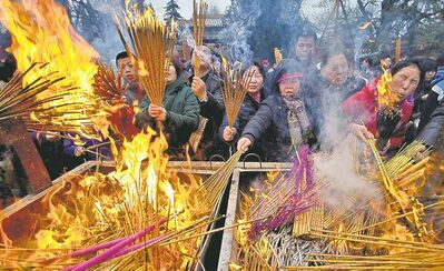 Andy Wong / The Associated PressTemple-goers burn incense as they pray for health and fortune on the first day of the Chinese Lunar New Year at Yonghegong Lama Temple in Beijing Sunday. Millions across Asia are celebrating the Year of the Snake.